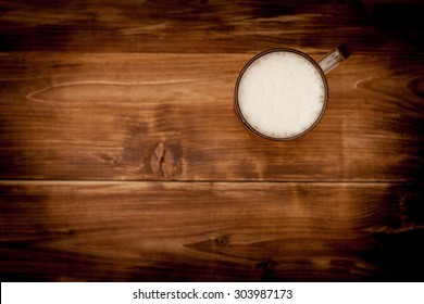 A glass of beer on the background of the wooden planks.