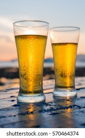 Glass of beer on a beach at sunset