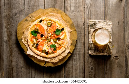 Glass of beer on a birch stand and the pizza on the wooden table. Top view