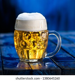 Glass of beer on the blue wooden background.