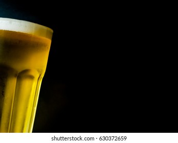 A glass of beer on dark background