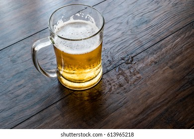 Glass of Beer on dark wooden surface.