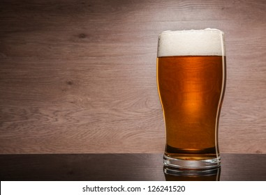 Glass with beer on the table.