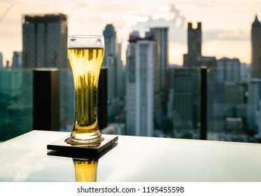 Glass of beer on table in rooftop bar with blur bangkok skyline in background, Thailand.
