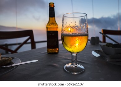 Glass of beer on a table of  seaview restaurant at sunset on the island of El Hierro, Canary Islands, Spain
