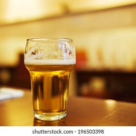 A glass of beer on top of a brown surface.
