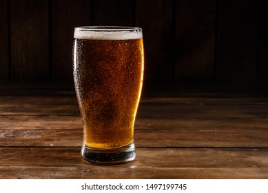 Glass beer on wood background with copy space. Full glass with lager beer, close up. Glass of alcohol