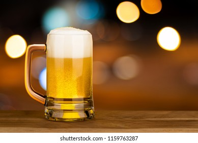 Glass of beer on wood table in pub with bokeh light night background , drinking alcohol celebration concept design with copy space