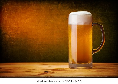 glass of beer on wood table with grunge wall