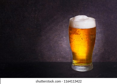 Glass of beer on wooden background with copyspace for text