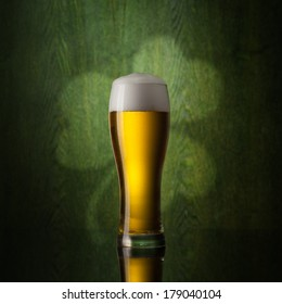 glass beer on wooden background with st.patrick logo