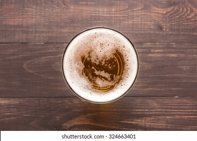 glass of beer on a wooden background. Top view.