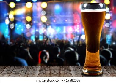 Glass of beer on a wooden background concert lights bokeh.Concept Festive Celebrations.
