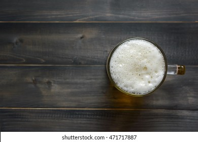 glass beer on wooden background with copy space, top view
