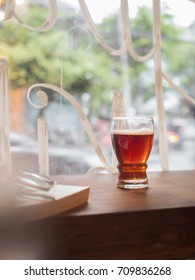 A glass of beer on wooden counter with daylight from window in the evening. Background outside is the street.