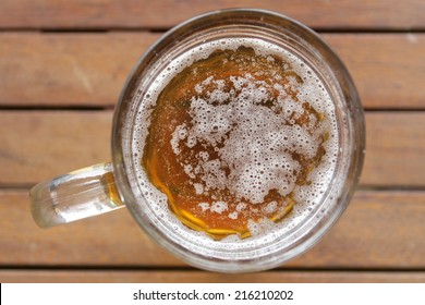 glass of beer on wooden desk top view