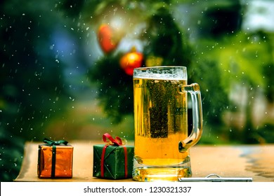 Glass of beer on wooden table with snow, and gift box.