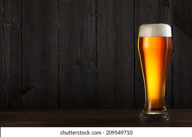 Glass of beer on wooden table, dark background with copy space