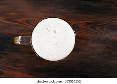 Glass of beer on wooden table, top view