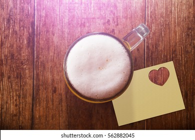 Glass of Beer on the Wooden Table at Bar with Blank Paper Note and Heart Shape, Top view