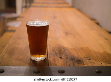Glass of beer on wooden table in pub background