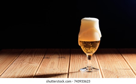 A glass of beer on a wooden table, dark background, Copy space