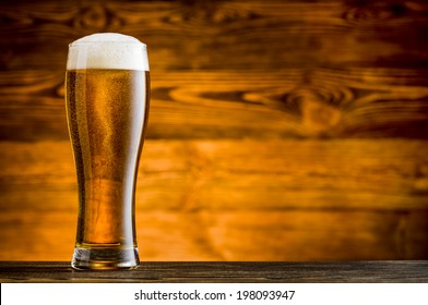 Glass of beer on woodend table and wooden background