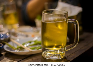Glass of beer place on wood table.