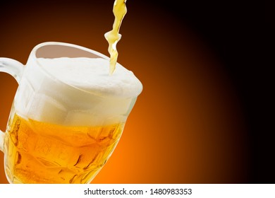 A glass of beer is poured close-up. Place for text.