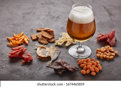 Glass with beer and set of various kind snacks: jerky,  potato chips, salted nuts, stockfish, bread spicy crackers, dried squids  on dark gray background. Snacks for beer.