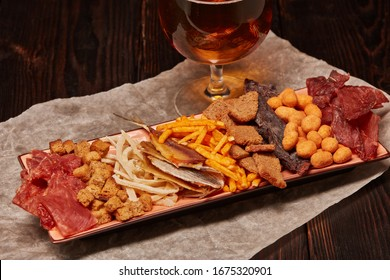 Glass with beer and set of various kind snacks: jerky,  potato chips, salted nuts, stockfish, bread spicy crackers, dried squids  on dark wooden background. Snacks for beer.