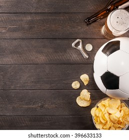 glass of beer. snack and soccer ball with copy space. Wooden background