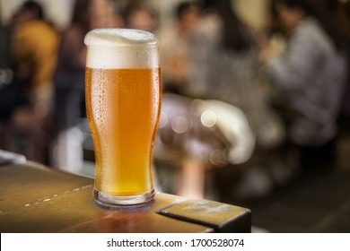 Glass of beer stands on a table in a pub. White unfiltered beer.