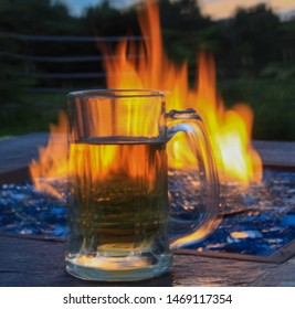 Glass Beer Stein resting on Firepit table lit with beautiful blue glass rocks, with dusk sky in background