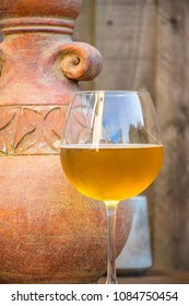 Glass of beer and stone jug in garden,soft,timber background,natural light,uk.Alcoholic drink,beverage,ale,lager.Ancient motive,theme.Beer on the table,outdoor,old  pottery,stoneware clay jug.
