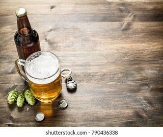 glass of beer with stoppers and a bottle opener. On a wooden table.