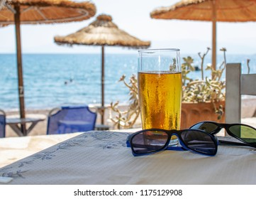 A glass of beer and sunglasses on a table at a touristic resort.Holidays and relax concept.