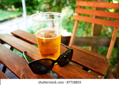 glass of beer and sunglasses standing on a wooden table