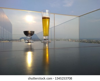 Glass of beer at sunset on a table of a rooftop bar