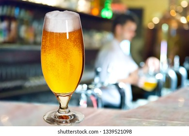 Glass of beer with waiter  in the pub