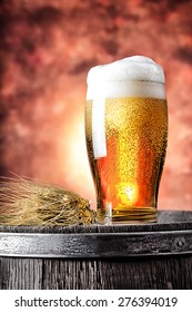 Glass of beer with wheat ears on a wooden barrel