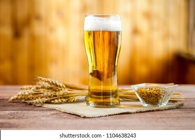 glass of beer with wheat on a wooden table background
