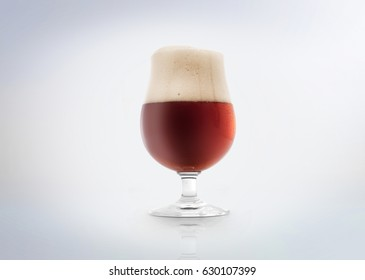 Glass of a belgian amber ale beer with foam. Isolated on white background.