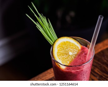 Glass of berry smoothie decorated with grass and lemon slice