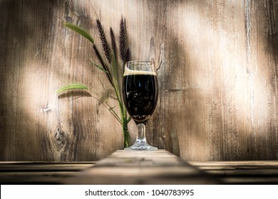Glass of black beer with foam, with wood, streaks and spikes behind.