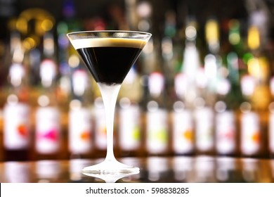 Glass of black russian cocktail at bar counter background.