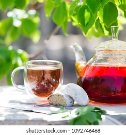Glass of black tea in double bottom glass under the shade of the tree with green leaves under sun light, summer hot drink with glass kettle of strong tea on wooden table and tea cloth, copy space