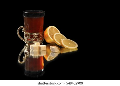 A glass of black tea with lemon and slices Thatched sugar on a black background with reflection. Tea is poured into a glass with a cup holder