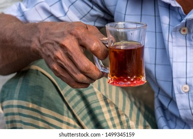 A glass of black tea in the wrinkled hand of a man.