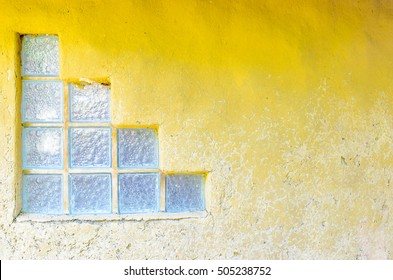 Glass block on the old yellow cement wall